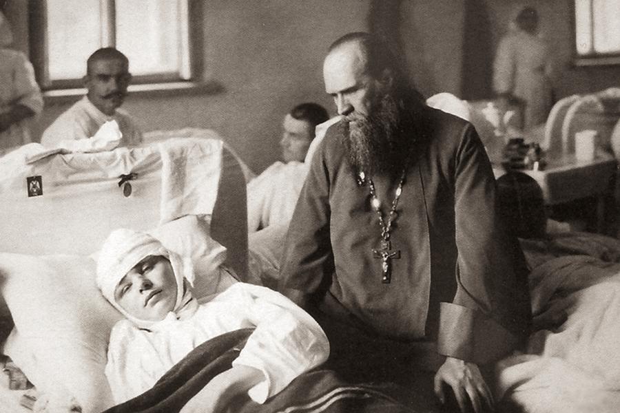 Протоиерей Александр Васильев у постели раненого